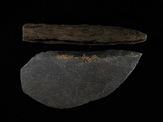 A dark grey stone shaped into a sharpened semi-circle, with the wooden handle detached.