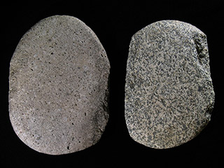 Two large grey stones, the left one smooth and the right one pitted along the edges, are sitting on a black background.
