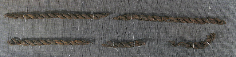 Three pieces of reddish brown fibre are woven into a braid to create a cord.