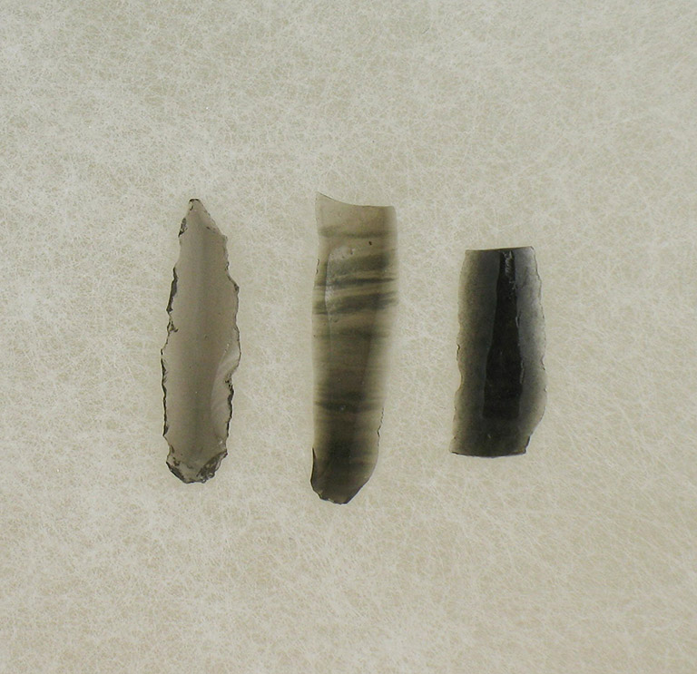 Three thin pieces of translucent rock are shaped into flat blades. They are varying shades of black to grey.