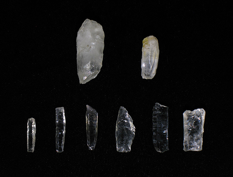 Eight thin pieces of translucent rock are shaped into flat blades. They are varying shades of black to grey.