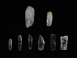 Eight small pieces of translucent light-coloured rock are laying on a black background. Many are shaped into small blades.