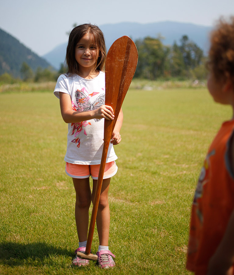 Young girl holding a paddle that is as tall as her.