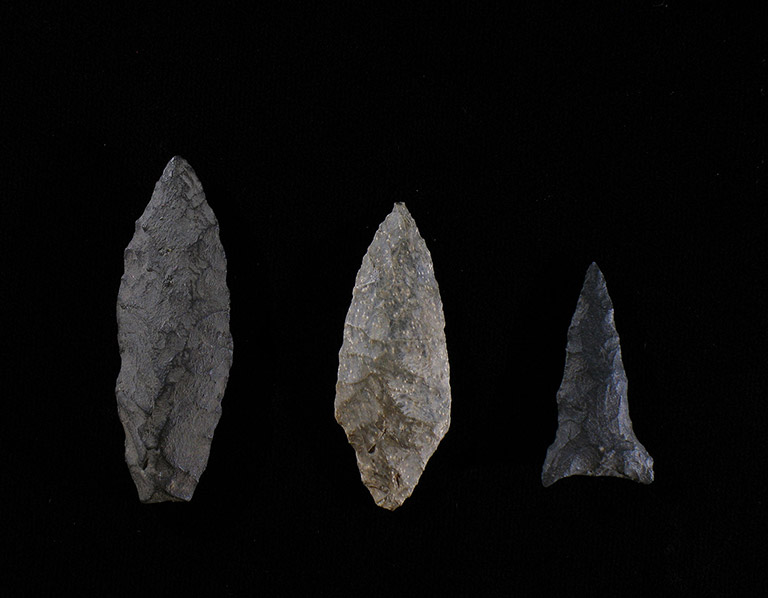Three arrowheads of different sizes, in various shades of grey, on a black background.