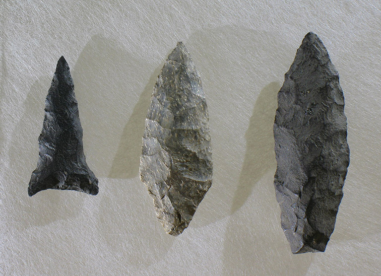 Three arrowheads of different sizes, and various shades of grey, on a white background.