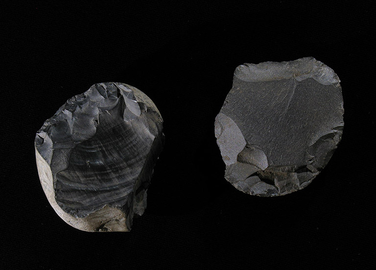 Two round, dark grey stones, with sharpened edges and smooth tops.