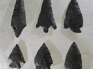 Six arrowheads of different sizes and widths made of dark stone on a white background.