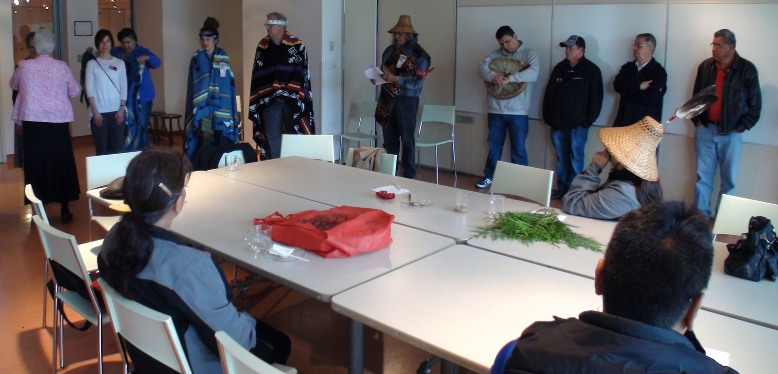 A red bag and some cedar boughs lie on a table. Three people sit at the table, while others stand alongside.