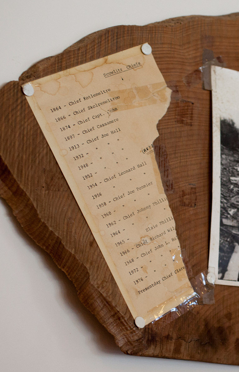 "An old ripped piece of paper and a black and white photograph are taped to a piece of wood. The old piece of paper is a list of ""Scowlitz Chiefs."" The black and white photograph is of a river bank and forest."