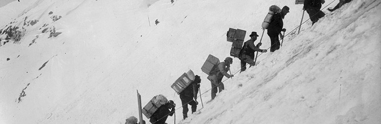 A black and white photograph shows men hiking up a steep snow-covered slope. Each man carries a large pack on his back.