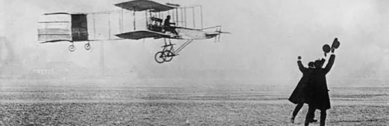 A biplane flies just above the ground. Two men in the foreground have their arms up and hats in the air in celebration.