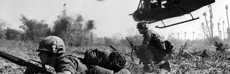 Soldiers lying flat on the ground with a helicopter above them