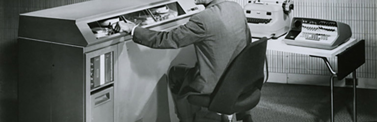 Man sitting in an office with two typewriters and massive square machine with buttons and dials