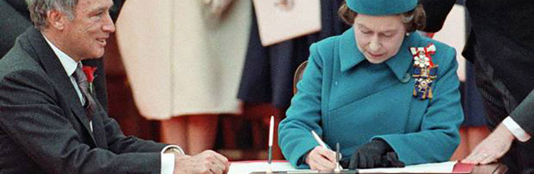 Queen Elizabeth, dressed in a blue hat and coat, signs a document with the Canadian Prime Minister.