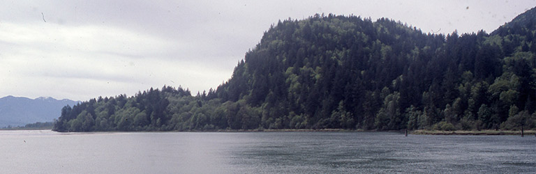 A grey river in the foreground with a hill in profile across the water, low and then rising to a hump