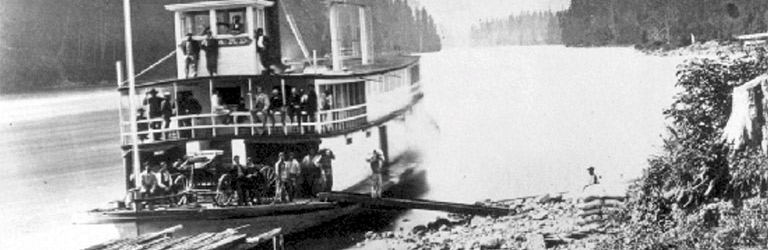 The stern of a paddlewheel boat is pulled close to a rocky shore on the Fraser river, with people on board. There are trees on both sides of the river.
