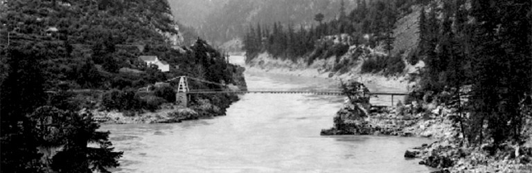 A black and white photograph of a bridge crossing the Fraser River.  The banks of the river are rocky with trees growing up the slopes.