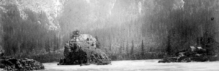 A black and white photograph of a large rock in the middle of the Fraser River with large mountains in the background.