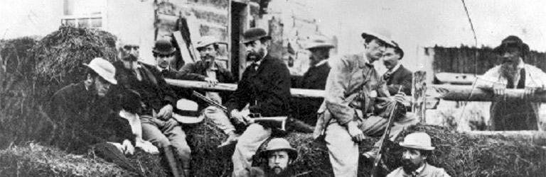 A group of nine men with their guns resting on hay bales sit in front of a house.