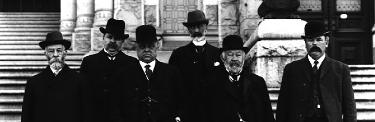 Six men in suits and hats standing in front of a set of stairs
