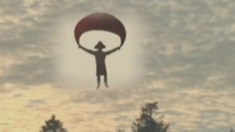 A figure with a cedar-root hat descends through the sky holding a parachute.