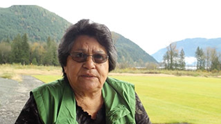 An elder talks to the video camera outside. There are mountains and trees in the background.