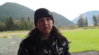 A woman shares her story with a video camera. She sits outside with the mountains and trees behind her.