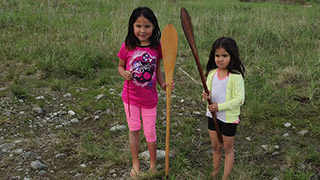 Two young girls pose on the grass with their canoe paddles.