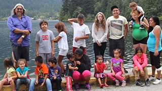 A group of children and young adults pose with their elder for a photograph on the shore of the river. There are mountains and trees in the background.