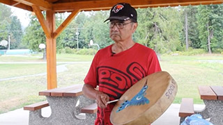 A man stands outdoors playing a hand drum. The drum is decorated with the image of a blue hummingbird.