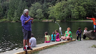 An elder shares a story with children and community members near the shore of the river.