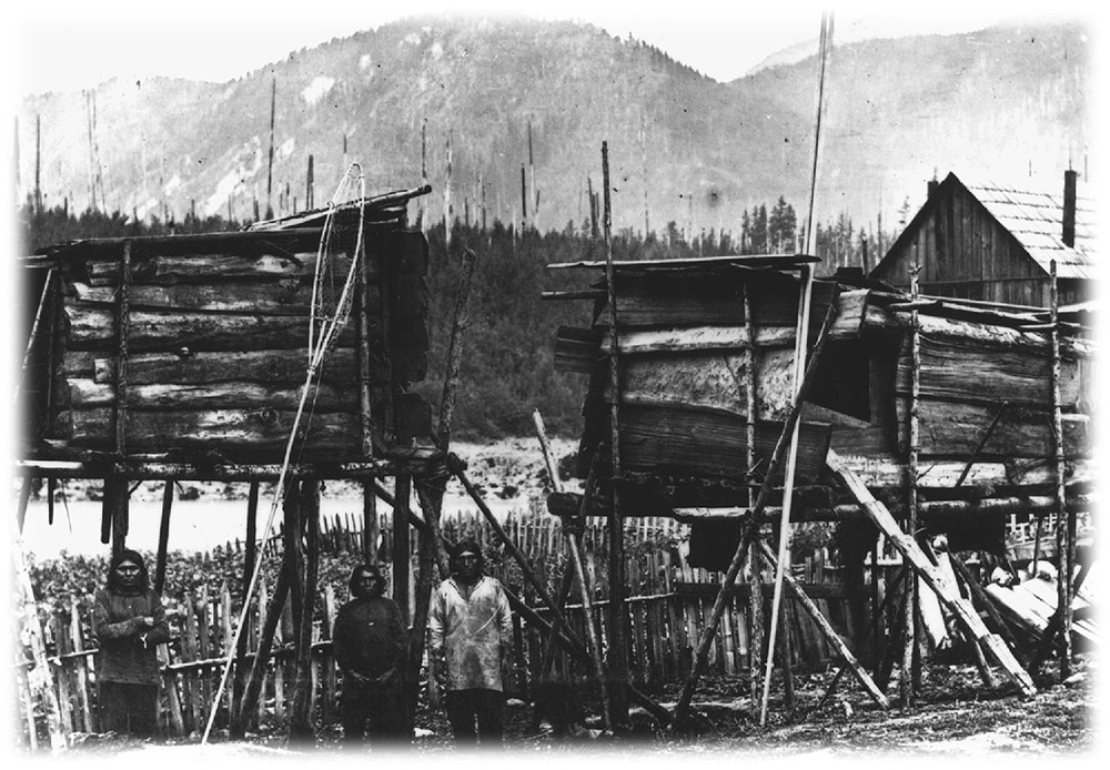 A black and white photograph of raised storage boxes on wooden stilts. There are several men standing in the foreground, and snow-capped mountains in the background.