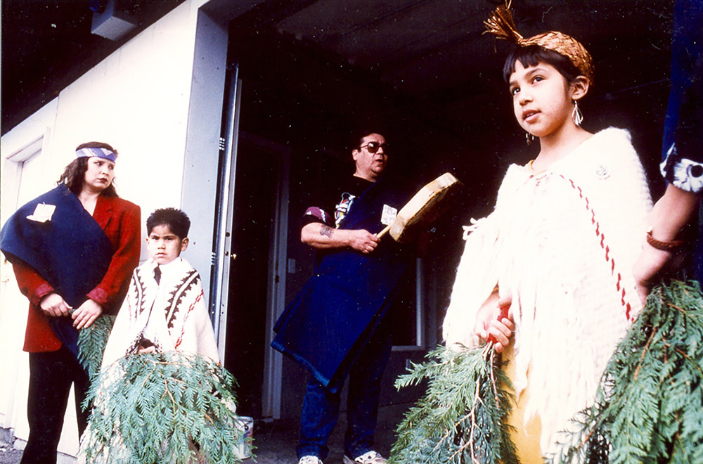 There are two young children dressed in regalia, holding onto cedar branches. A man and woman stand close by.