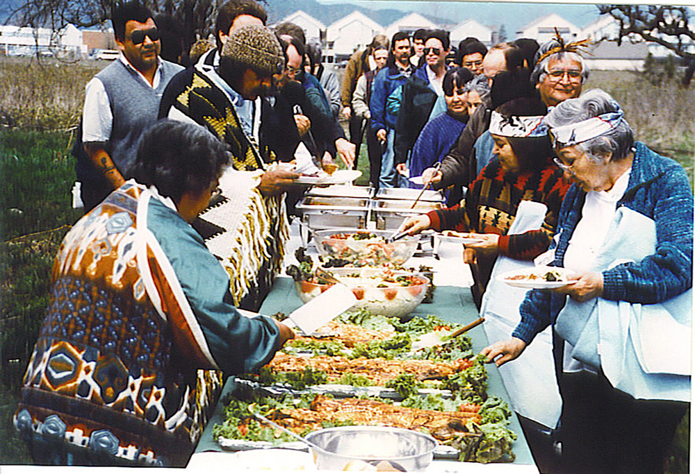 A large group of people are gathered outside, lined up around a long table that is covered in many dishes of food at a First Salmon Ceremony.