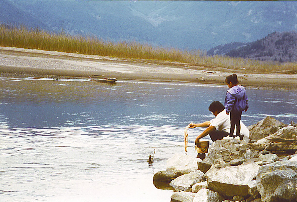 A man and young girl are gathered by the edge of the river; the man is crouching down with an object in his hand, while the girl stands beside him looking onwards.