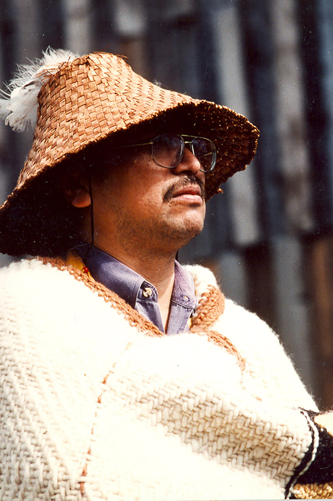 A photograph of a man wearing a woven hat and blanket.