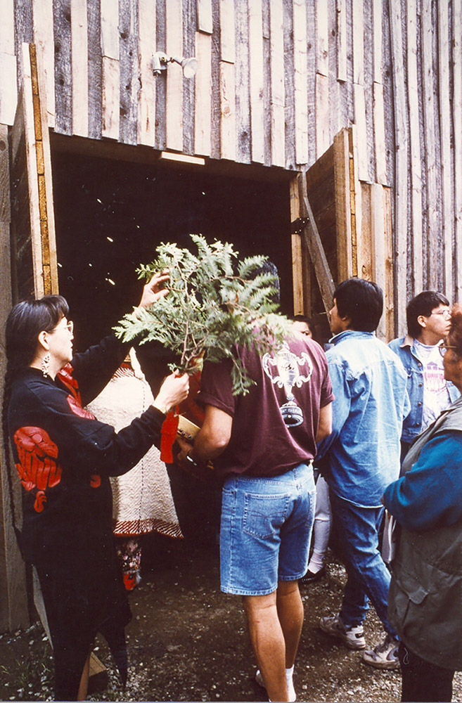 A group of people are gathered outside of a wooden building; they are being brushed with a cedar branch before entering the building.