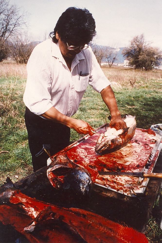 A man stands over a table set up outside; he is preparing salmon for cooking.