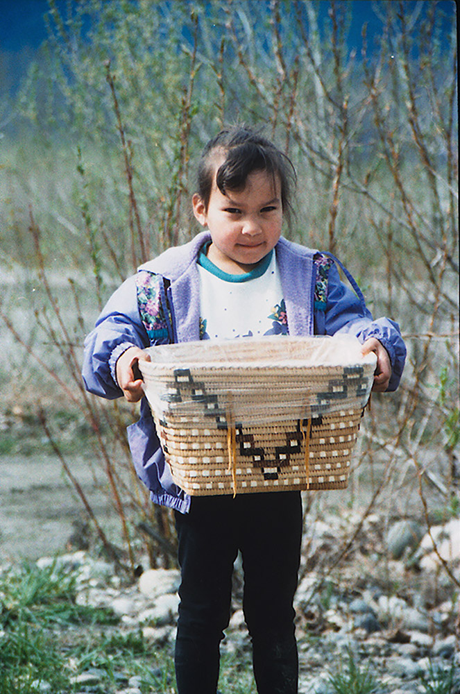 "A young girl stands outside, holding onto a medium-sized woven basket with both hands. The basket has a design in the shape of a ""V"" on the front."