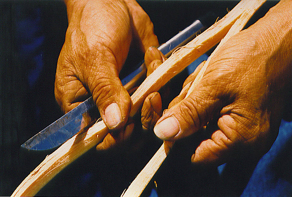A man uses a knife to separate a cedar root into two halves, still attached at the base.