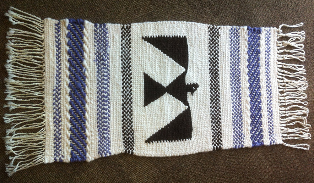 Weaving with white and blue stripes and a thunderbird design.