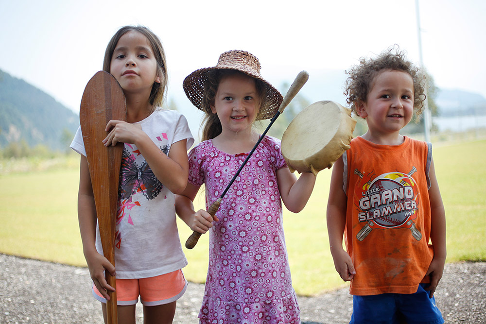 Three young children stand outside. The girl on the left holds a paddle upright, touching her chin. The girl in the middle holds a drum. The boy on the right smiles at the camera.