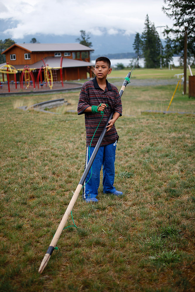 A young boy stands on the grass, holding his homemade fishing spear.