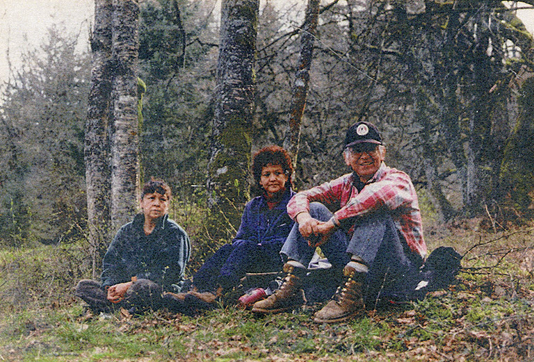 Three adults are sitting on the grass outside, with trees behind them.