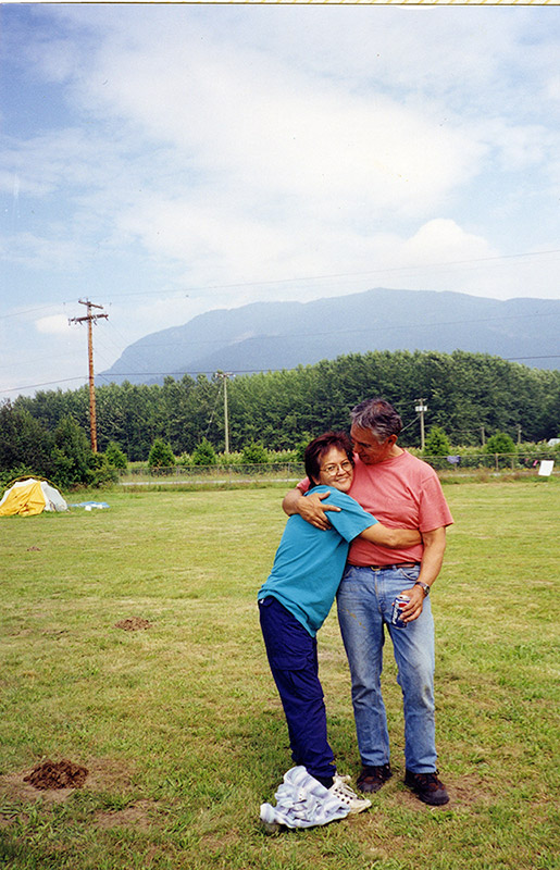 A woman and man stand outside on the grass. She has her arms wrapped around the his waist, and is facing the camera. He is looking at her.