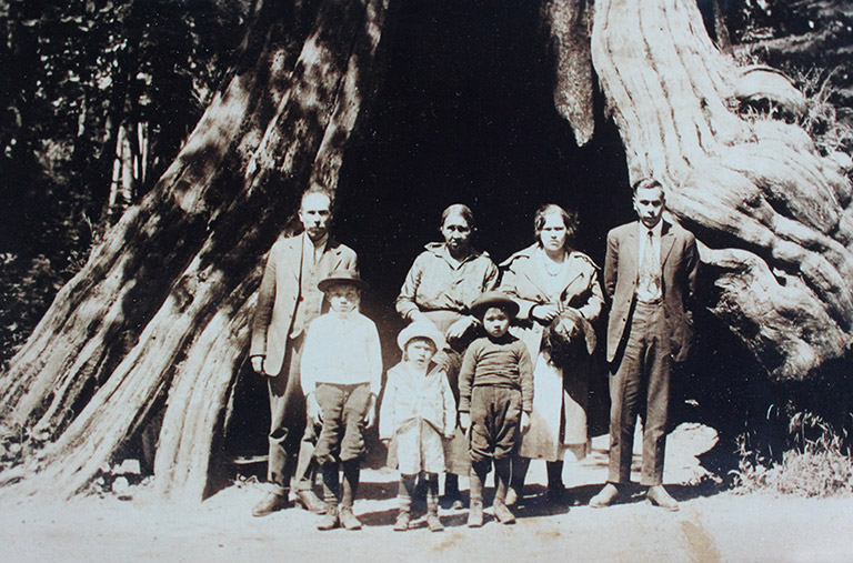 A family poses in front of the trunk of a very large tree. Four adults stand in the back, and three children stand in front.