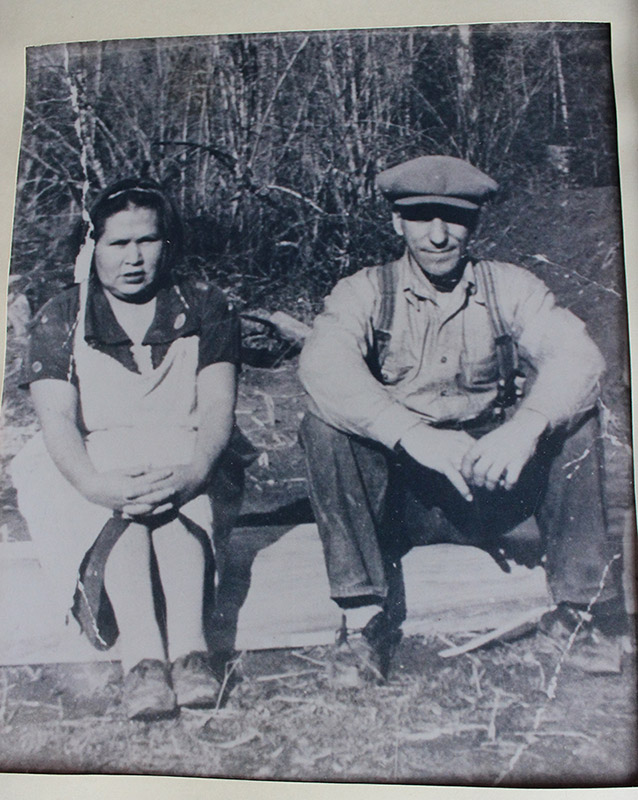 A black and white photograph of a young couple sitting side-by-side on a blanket on the grass outside.