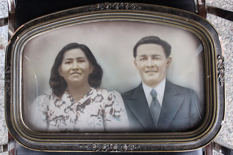 A framed photograph of a young couple. The frame is dark silver, with some ornate details on the sides.