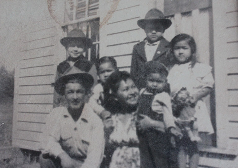 A black and white photograph of a family. The man and woman stand in front, with four children standing behind. The woman holds the youngest child beside her.