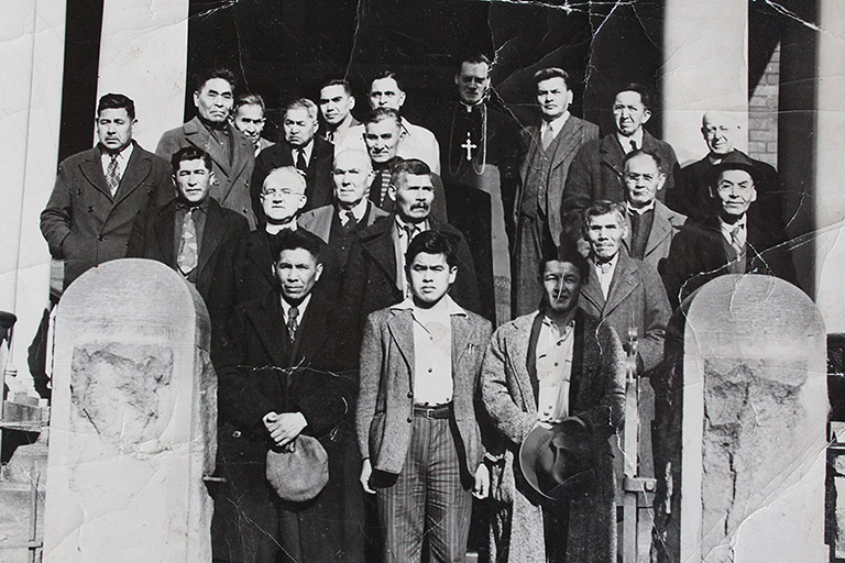 A black and white photograph of a group of twenty men. They are standing outside a building in three rows, and wearing formal suits.